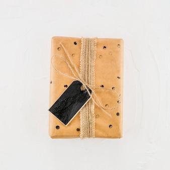 Geschenkbox im kraftpapier mit schwarzem tag