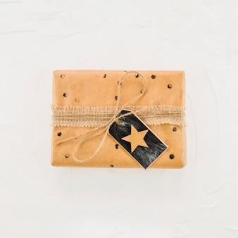 Geschenkbox im kraftpapier mit stern auf schwarzem tag