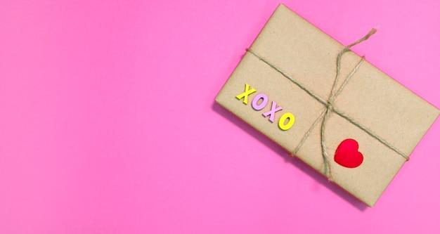 Geschenkbox in bastelpapier mit rotem herzen und xoxo-wort auf rosa