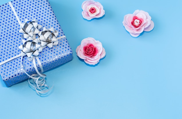 Geschenkbox in blauem papier auf blau verpackt. valentinstag, feiertag und geschenke.