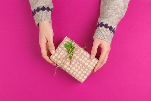 Geschenkbox in den weiblichen händen auf rosa