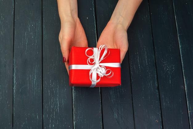Geschenkbox in der hand mädchen auf holztisch