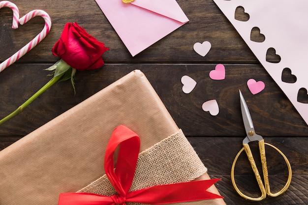 Geschenkbox in der nähe von blüte, umschlag und zuckerstangen