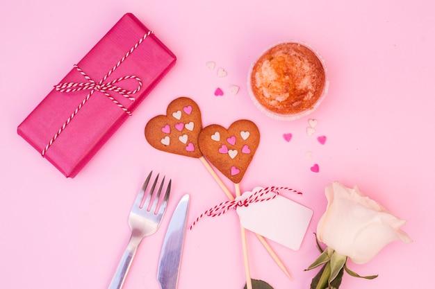 Geschenkbox in der nähe von kuchen, blumen und keksen auf zauberstäben