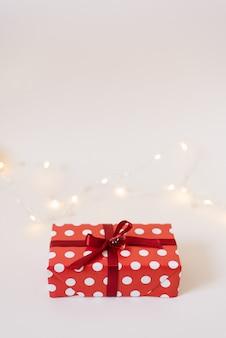 Geschenkbox in der roten papierverpackung mit den weißen tupfen, gebunden mit einem roten satinband mit einem bogen und einem glasherzen auf weiß
