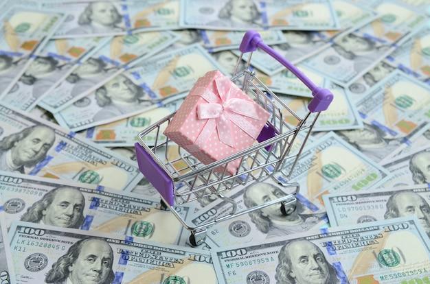 Geschenkbox in einem kleinen einkaufswagen liegt auf vielen dollarnoten