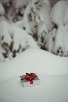 Geschenkbox in einer verschneiten landschaft