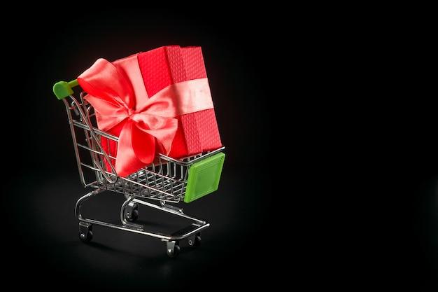Geschenkbox in festlicher verpackung mit satinschleife im warenkorb.