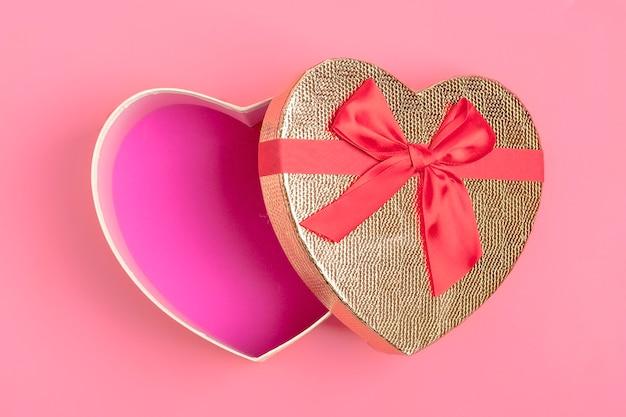 Geschenkbox in form eines herzens auf einem rosa hintergrund. alles gute zum valentinstag-konzept.