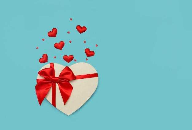Geschenkbox in form eines herzens mit einer roten schleife an einer blauen wand