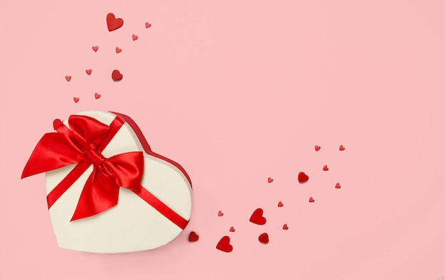 Geschenkbox in form eines herzens mit einer roten schleife an einer rosa wand.
