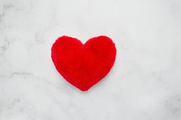 Geschenkbox in form eines herzens mit einer roten schleife auf einem weißen tisch.