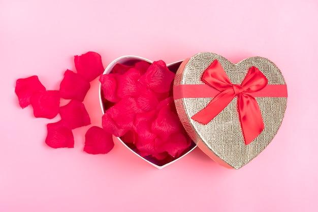 Geschenkbox in form eines herzens mit rosenblättern im inneren auf einem rosa hintergrund happy valentinstag-konzept