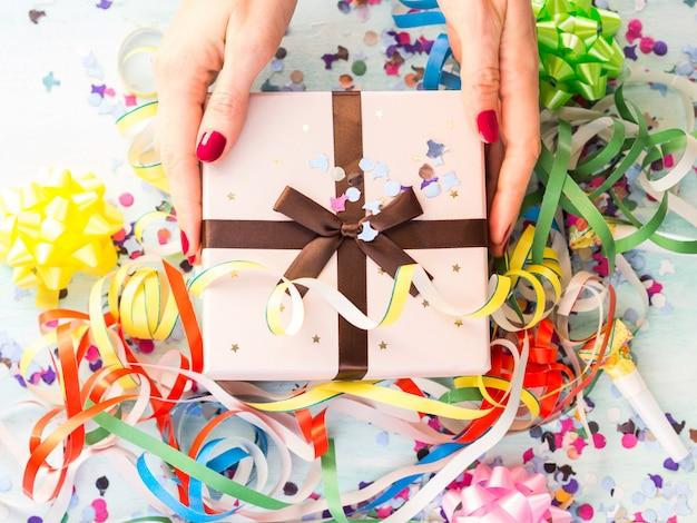 Geschenkbox in händen über luftschlangen und konfetti