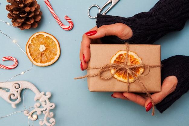 Geschenkbox in händen und weihnachtsschmuck