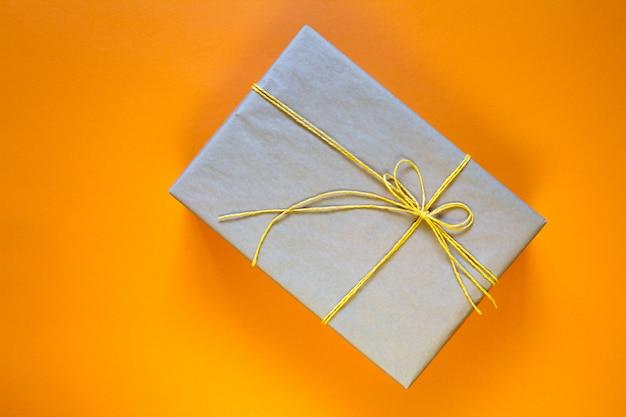 Geschenkbox in recyceltem papier mit gelber schnur umwickelt