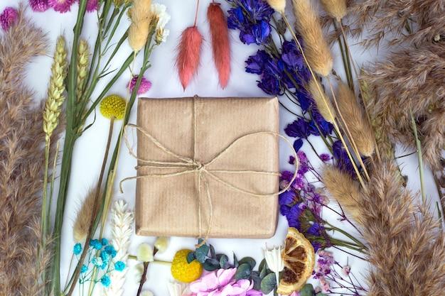 Geschenkbox in umweltfreundlichem bastelpapier, umgeben von bunten frischen trockenblumen draufsicht