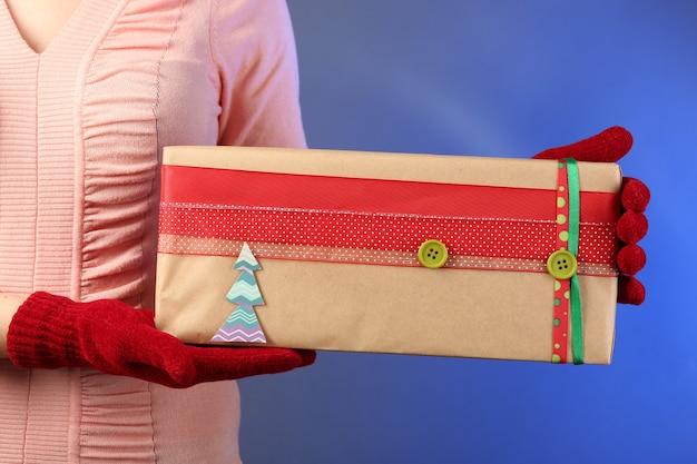 Geschenkbox in weiblicher hand an farbwand