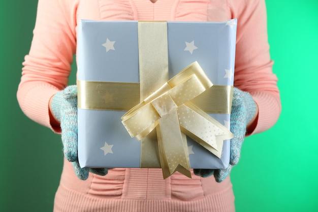 Geschenkbox in weiblicher hand auf farbigem hintergrund