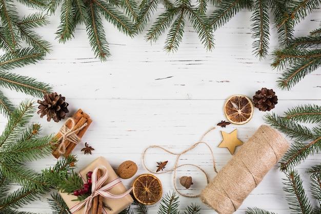 Geschenkbox in weihnachtsverpackung in der nähe einer garnrolle zwischen tannenzweigen