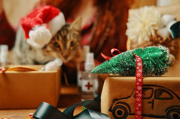 Geschenkbox mit auto und weihnachtsbaum auf dach katze in weihnachtsmann-hut auf hintergrunddesinfektionsmitteln für hyg...