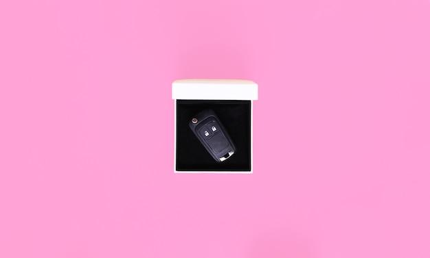 Geschenkbox mit autoschlüsseln auf rosa hintergrund. flache lage, draufsicht, kopierraum. konzeptauto, autovermietung, geschenk, fahrstunden, führerschein.