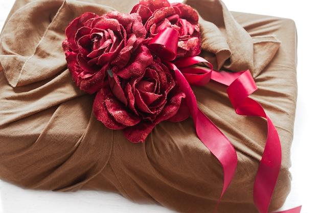 Geschenkbox mit bändern und dekorativen rosen auf strickwaren