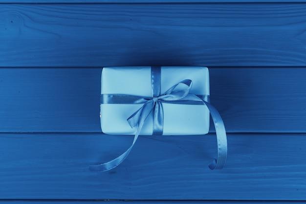 Geschenkbox mit band auf blauem hintergrund, draufsicht