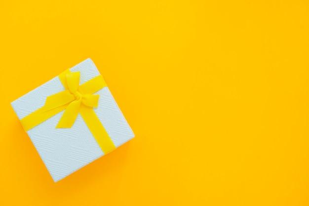 Geschenkbox mit band auf draufsicht des gelben hintergrundes