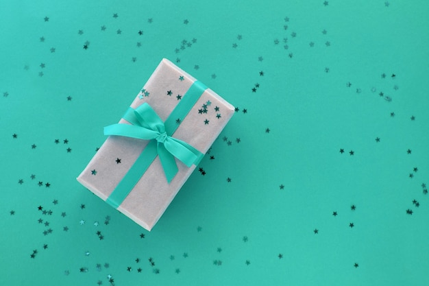 Geschenkbox mit band- und konfettidekorationen auf buntem hintergrund des pastellpapiers. flache lage, draufsicht, kopierraum