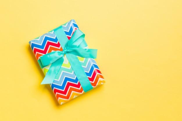 Geschenkbox mit blauem bogen für weihnachten auf gelb