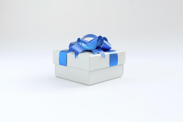 Geschenkbox mit blauem farbbogenknoten und -band lokalisiert auf weißem hintergrund