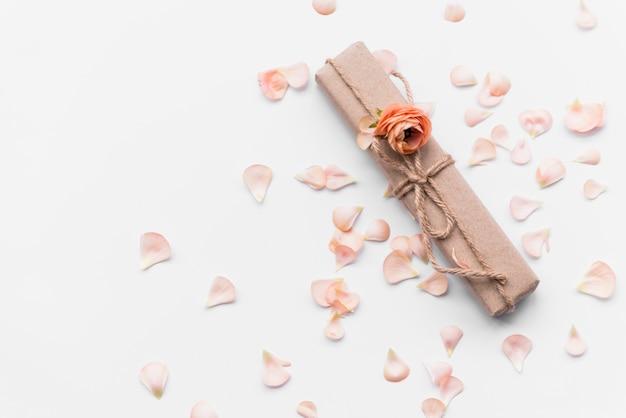 Geschenkbox mit blume unter blütenblättern