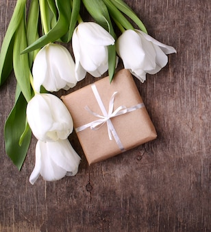 Geschenkbox mit blumen (weiße tulpen) auf rustikalem hölzernem hintergrund