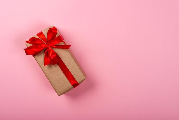 Geschenkbox mit bogen auf rosa neonhintergrund
