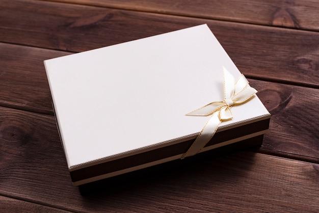 Geschenkbox mit bogen für jahrestag oder weihnachten auf einem dunklen holztisch