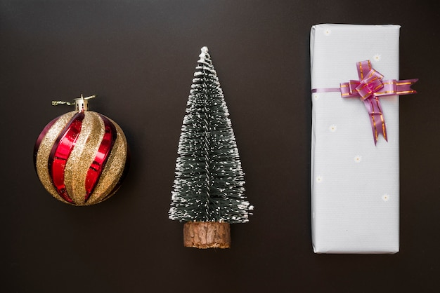 Geschenkbox mit bogen nahe dekorativem ball- und tannenbaum
