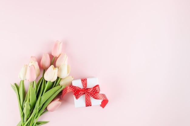 Geschenkbox mit bouquet ulips auf pastellrosa hintergrund. frühlings- oder urlaubskonzept