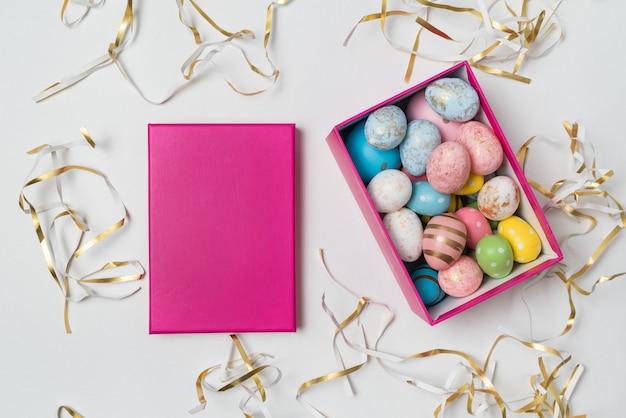 Geschenkbox mit bunten ostereiern auf weißem hintergrund. draufsicht