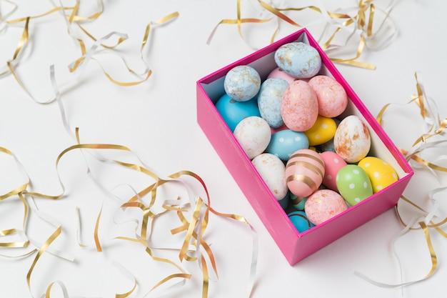 Geschenkbox mit bunten ostereiern. weißer feiertagshintergrund. draufsicht