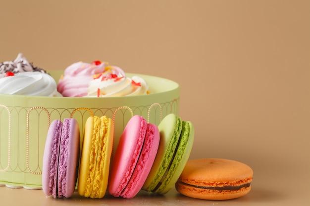 Geschenkbox mit cupcakes und buntem macaron auf beige