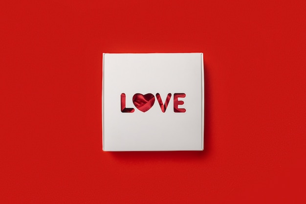 Geschenkbox mit dem text liebe auf einem roten hintergrund. zusammensetzung valentinstag. banner. flache lage, draufsicht.