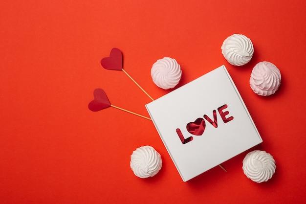 Geschenkbox mit dem text liebe, süßigkeiten und herzen auf einem stock auf einem roten hintergrund. zusammensetzung valentinstag. banner. flache lage, draufsicht.