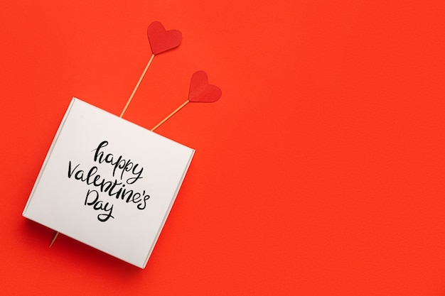 Geschenkbox mit dem text liebe und herzen auf einem stock auf einem roten hintergrund. zusammensetzung valentinstag. banner. flache lage, draufsicht.
