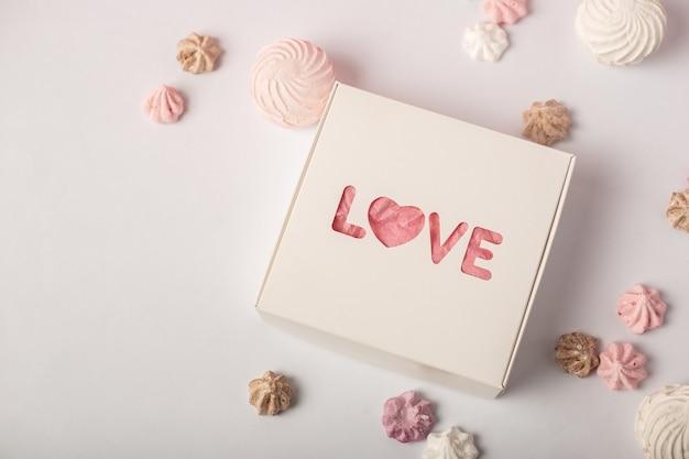 Geschenkbox mit dem text liebe und süßigkeiten auf hellem hintergrund. valentinstag geschenkkonzept. enger fokus. banner.