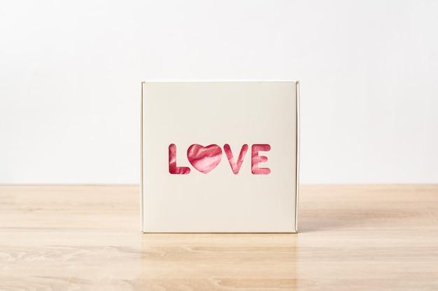 Geschenkbox mit dem text liebe. valentinstag geschenkkonzept. enger fokus. banner.