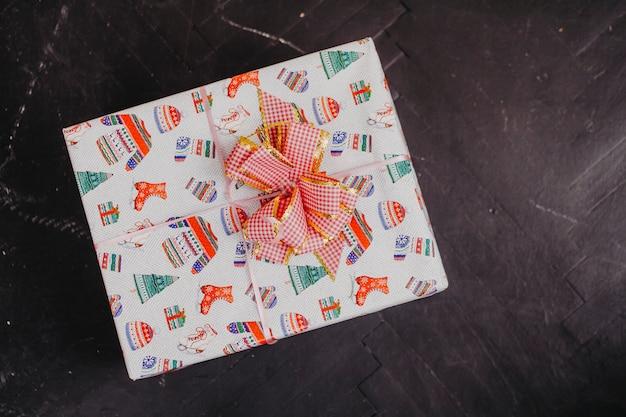 Geschenkbox mit draufsicht des bogens über ein schwarzes
