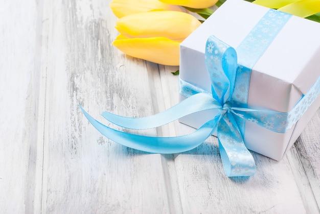 Geschenkbox mit einem blauen band und einem blumenstrauß von gelben tulpen auf einem holz