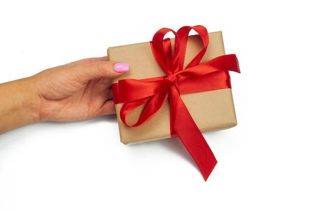 Geschenkbox mit einem bogen in den händen eines mädchens