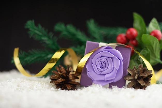 Geschenkbox mit einem lila bogen mit zweigen eines weihnachtsbaumes